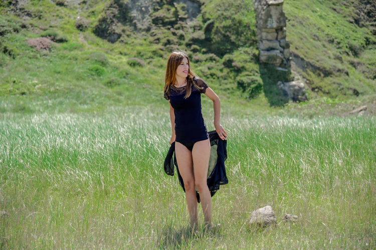 Full length of young woman standing on grass