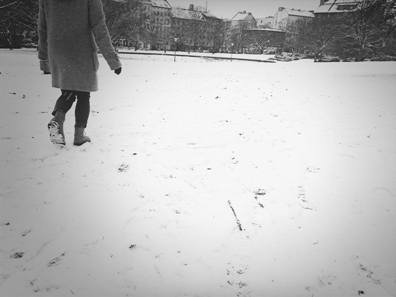 A young person walks alone in the snow
