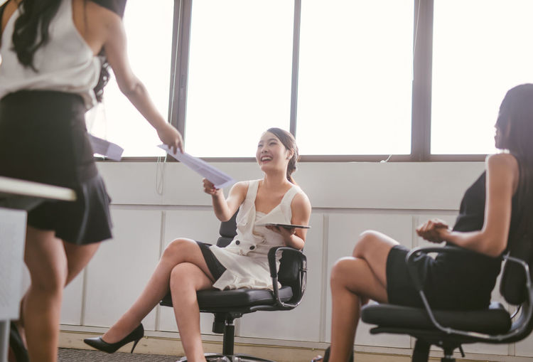 Business woman passing document to manager at the office .Smiling young asian girl working in office. Asian  Meeting Woman Work Working Adult Beautiful Woman Beauty Business Day Focus On Foreground Front View Girl Group Of People Indoors  Lifestyles Occupation People Real People Seat Sitting Three Quarter Length Women Young Adult Young Women