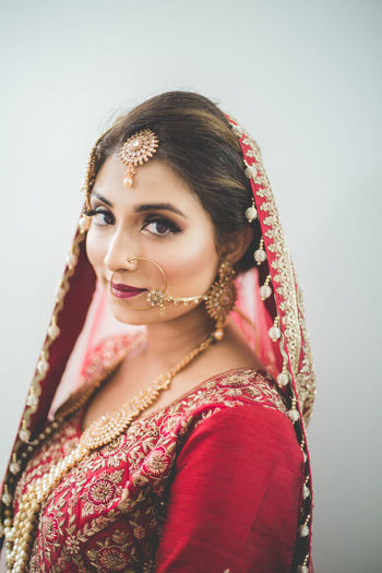 Portrait Of Beautiful Bride In Red Traditional Clothing Against White Background