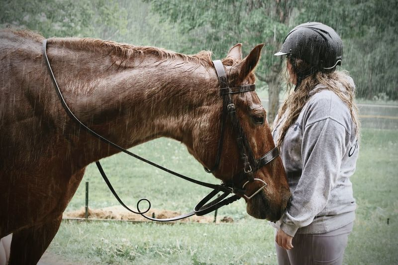 Girl standing in the rain with her horse