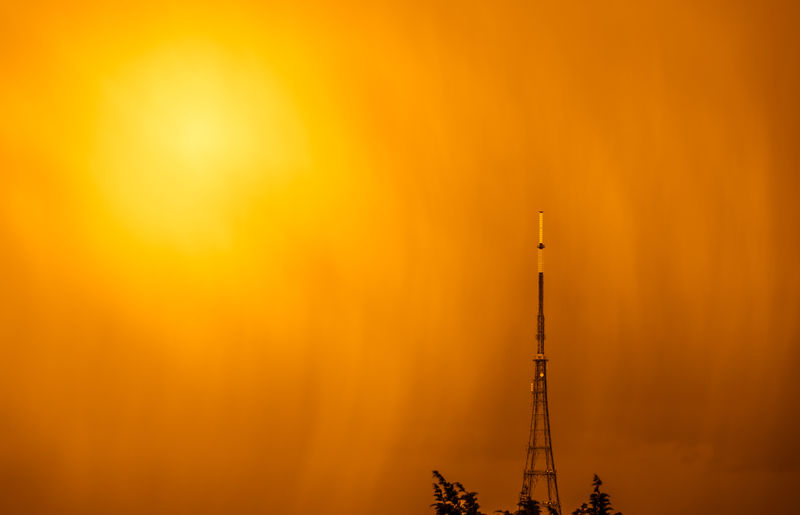 Silhouette of tower against orange sky