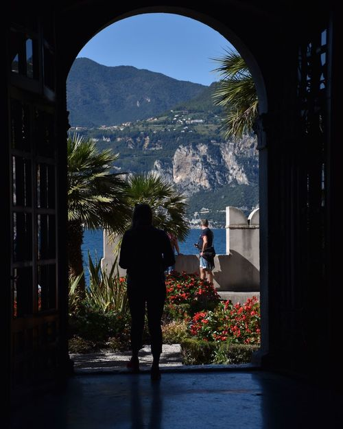 Real People Lifestyles Arch Leisure Activity Two People Day Architecture Full Length Window Women Togetherness Doorway Standing Plant Men Built Structure Outdoors Tree Nature Water Malcesine
