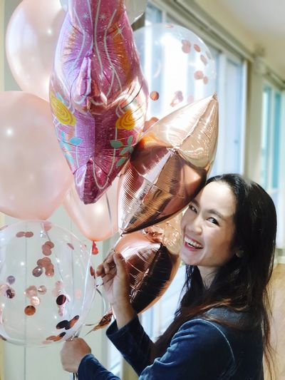 Portrait of smiling woman holding balloons