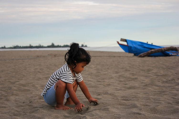 Boy on shore at beach against sky