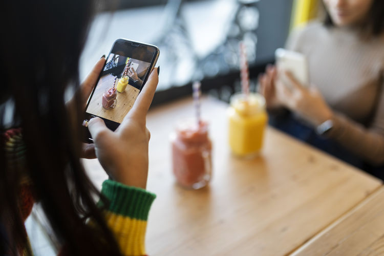 Midsection of woman using mobile phone on table
