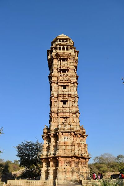 Low angle view of tower of victory Ancient Ancient Civilization Architecture Blue Built Structure Chittorgarh Fort Clear Sky Day Heritage Site History No People Outdoors Sky Tower Tower Of Victory Tree