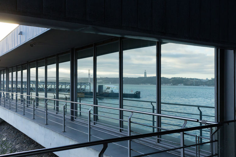 Reflection of tagus river against cloudy sky on sliding door