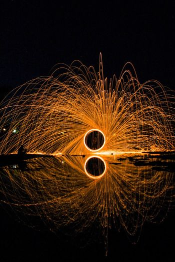 Reflection Of Burning Wire Wool On Lake At Night