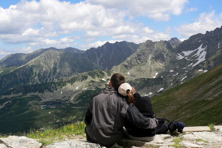 Rear view of man embracing woman while looking at mountains