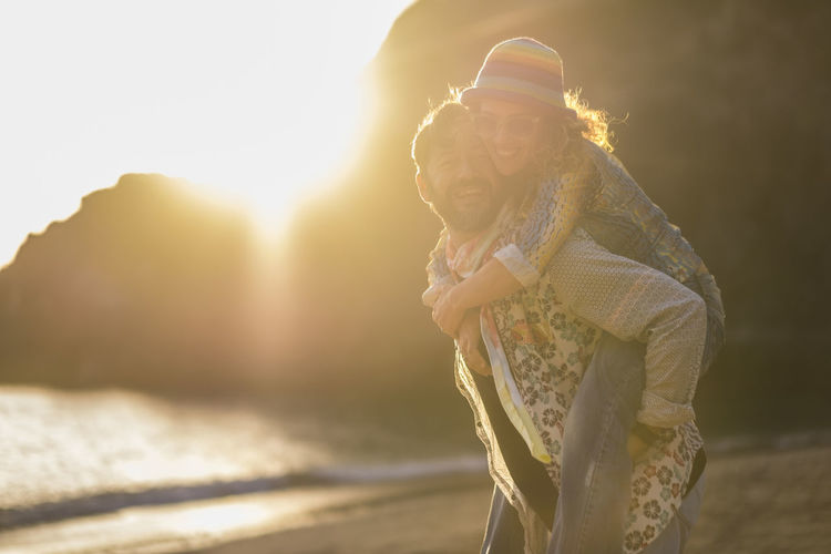 Man piggybacking woman while standing at beach against mountain during sunset
