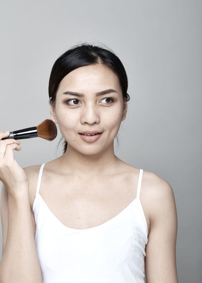 Smiling Woman Applying Make-Up With Brush Against Gray Background