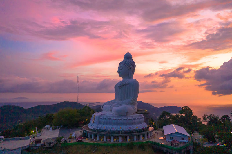 scenery sunset on Phuket big Buddha thunderstorm in sunset at Phuket big Buddha have beautiful color in the sky Phuket Big Buddha Sunset, Storm, Religion, Church, Sect, Denomination, Belief, Ideology, Creed, Teaching, Doctrine, Moslem, Islam, Statue, Statue's, David, Florence Tourism, Sky Cloud - Sky Sunset Architecture Religion Built Structure Spirituality Belief Building Exterior Nature Building Sculpture Statue Place Of Worship Representation Orange Color No People Human Representation Art And Craft Idol