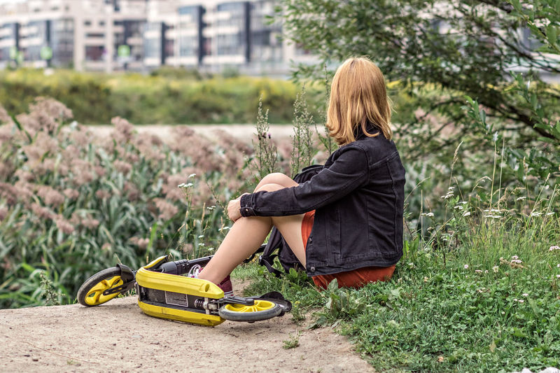 Young woman sitting in the green grass in the park. relaxing with scooter