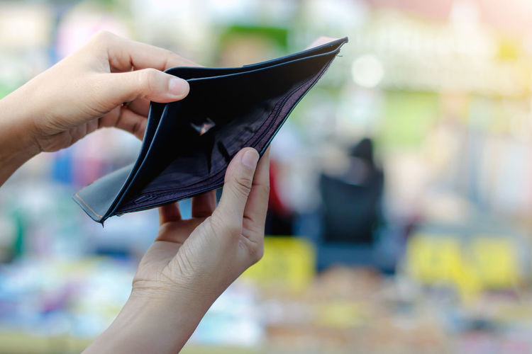Close-up of woman holding empty wallet outdoors