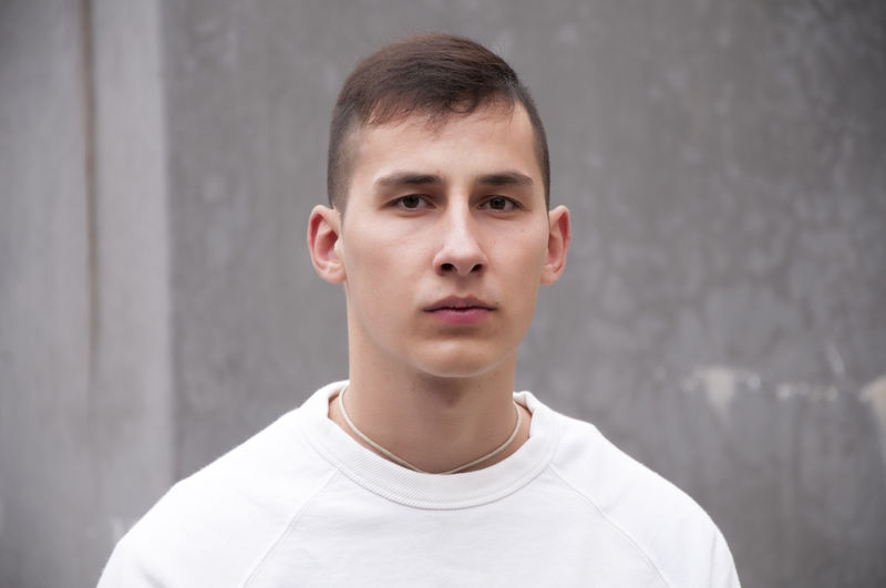 Portrait Headshot Front View One Person Looking At Camera Gray Young Adult Casual Clothing Lifestyles Gray Background Standing Wall - Building Feature Young Men T-shirt Close-up Day Focus On Foreground Confidence  Teenager Teenage Boys Adolescence  Contemplation