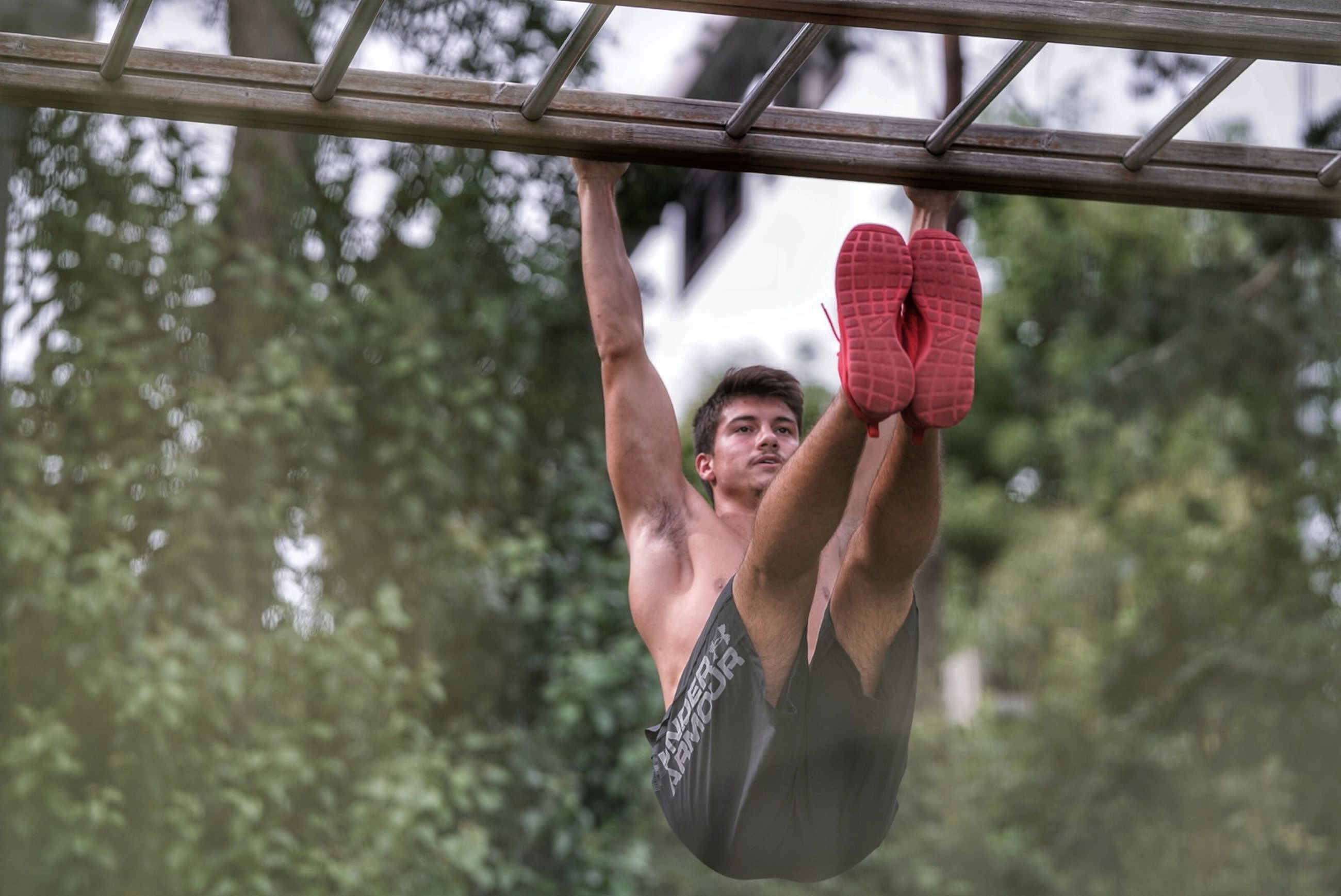 one person, shirtless, lifestyles, men, hanging, real people, sport, day, adult, strength, muscular build, clothing, vitality, young men, young adult, plant, healthy lifestyle, athlete, effort, outdoors