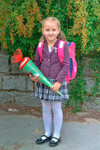 Child Childhood Full Length One Person Holding Girls Standing Portrait Looking At Camera Smiling Front View Happiness Plant Offspring Emotion Day Cheerful Females Innocence Outdoors School School Uniform