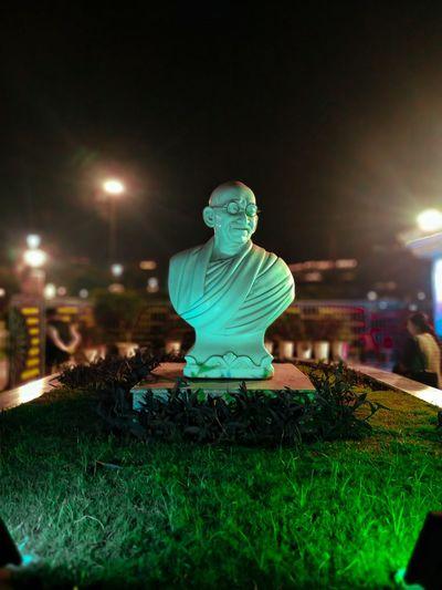 Man sitting in illuminated park at night