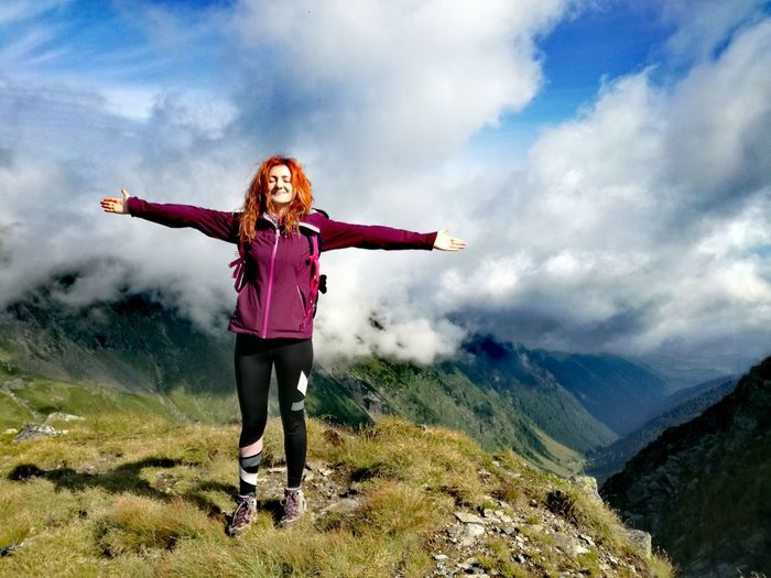 Full length of woman with arms outstretched standing on mountain against cloudy sky
