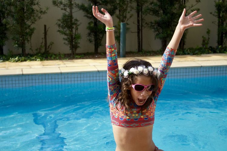 Low section of woman wearing sunglasses in swimming pool