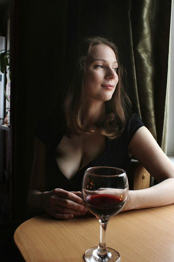 Smiling woman with wineglass on table sitting at restaurant