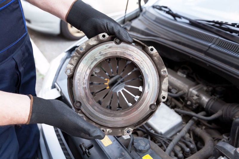 Auto mechanic wearing protective work gloves holds old clutch pressure plate over a car engine Automobile Spare Part Transmission Transportation Auto Auto Repair Shop Automotive Car Car Engine Car Service Clutch Clutch Pressure Plate Coupling Holding Human Hand Mechanic Mechanical Device Old Part Protective Glove Replacement Transportation Vehicle Working