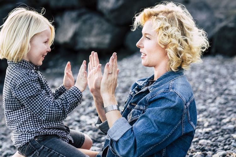 Side view of mother and son giving high-five at beach