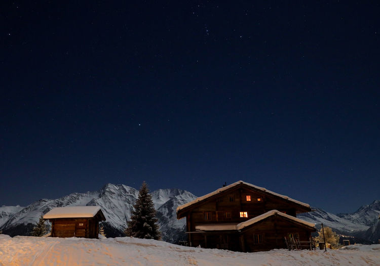 Snow covered houses against clear sky at night