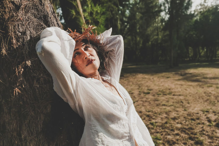 Thoughtful woman standing by tree trunk on land
