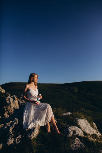 Woman sitting on rock against clear sky