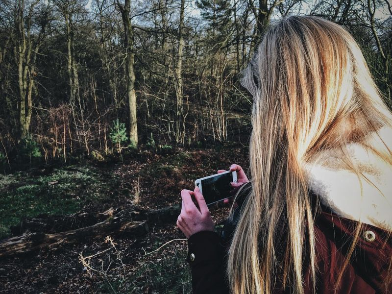 Real People Technology One Person Blond Hair Tree Holding Photography Themes Women Lifestyles Wireless Technology Headshot Leisure Activity Forest Outdoors Digital Camera Young Adult Day Nature Digital Single-lens Reflex Camera