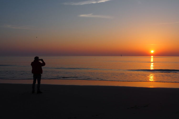 The Great Outdoors - 2018 EyeEm Awards Beach Beauty In Nature Horizon Horizon Over Water Land Leisure Activity Lifestyles Nature Nordsee One Person Orange Color Reflections Reflections In The Water Scenics - Nature Sea Silhouette Sky Standing Sun Sunset Sylt Unrecognizable Person Water
