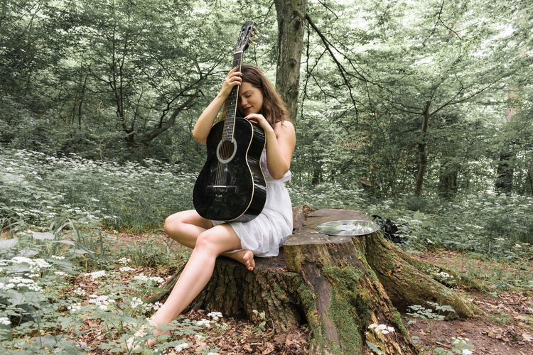 Young woman holding acoustic guitar while sitting on tree stump in forest