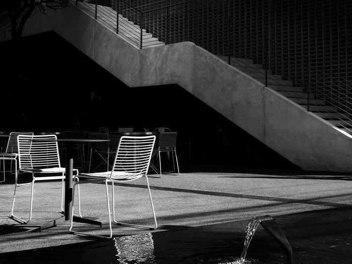 Beautiful light and shadow contrast of street furniture and staircase of a restaurant.