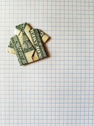 Close-Up Of Shirt And Necktie Made From Currency On Paper