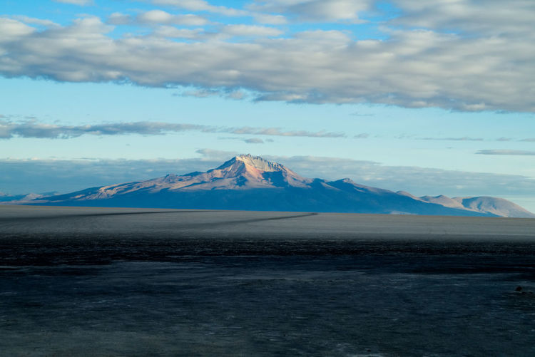 Beautiful morning light caption of the Cerro Tunupa from Isla Incahuasi in the middle of the Uyuni Salt Lake. The mix of shadows and sunlight touching the mountain in these early morning hours give the peak an even more fascinating touch. 2017 Beautiful Cerro Tunupa Dakar Isla Incahuasi Morning Light Star Wars Travel Uyuni Vacations Cloud - Sky Mountain Nature No People Outdoors Potosi Salar De Uyuni Salt - Mineral Salt Flat Salt Lake Scenics Sky Stunning Nature Traces