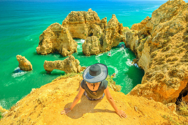 Summer holidays in Algarve, Portugal. Lifestyle tourist with hat sitting on promontory of Ponta da Piedade and overlooks the coast of Lagos with iconic cliffs and limestone. Turquoise sea, sunny day. Lagos Portugal Algarve Portugal Algarve Coastline Algarve Beach Algarve Cliffs And Beach Beach Sea Town Seascape Boat Portrait Pier Aerial View Cliff Jetty Boats Woman Females Girl Selfie Model Ponta Da Piedade Ponta Da Piedade Lagos Lighthouse Bay Water Rock Rock - Object Solid Lifestyles One Person Beauty In Nature Scenics - Nature Leisure Activity Real People Nature Rock Formation Day High Angle View Vacations Holiday Trip Turquoise Colored Outdoors
