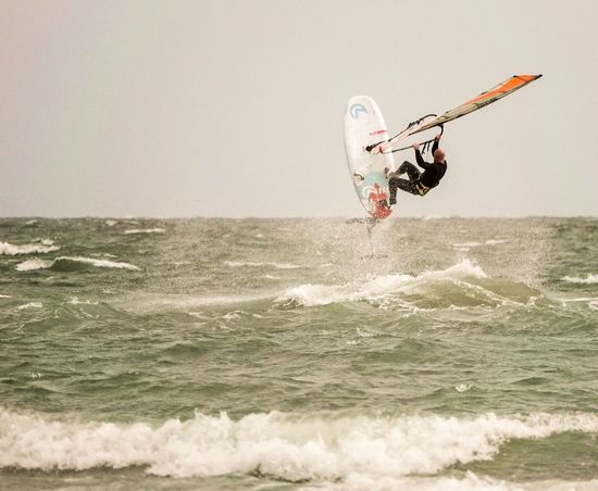 A windsurfer testing a new hydrofoil board off Hayling Island in Hampshire, UK. Watersports Jumping Jump Hayling Island  Windfoiling Windfoil Hydrofoiling Hydrofoil Windsurfer Windsurfing Windsurf Water Sea Motion Sport One Person Wave Leisure Activity Aquatic Sport Extreme Sports Adventure