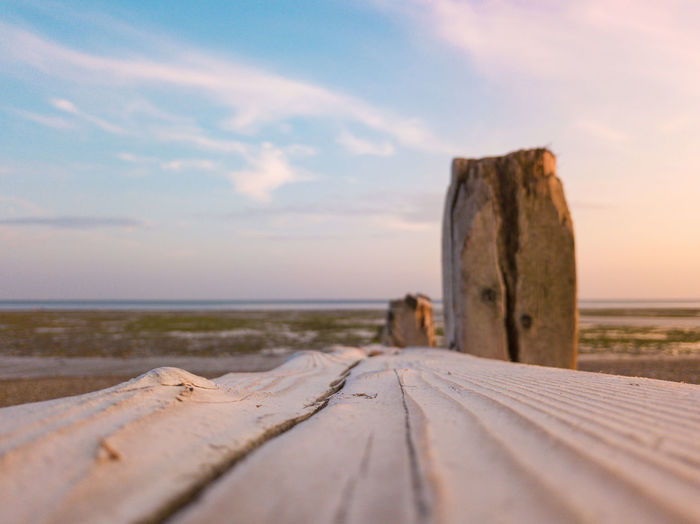 Surface level of wood at beach against sky
