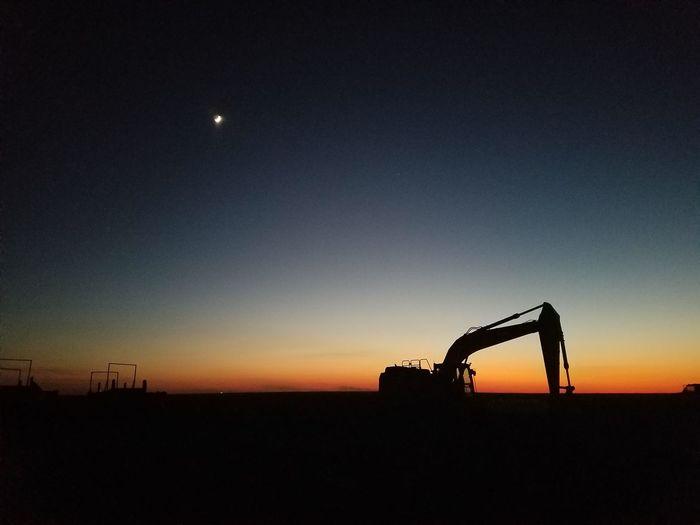 Silhouette Bulldozer On Field Against Sky During Sunset