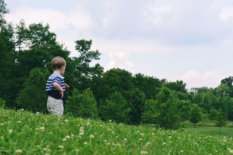 Boy on field against sky
