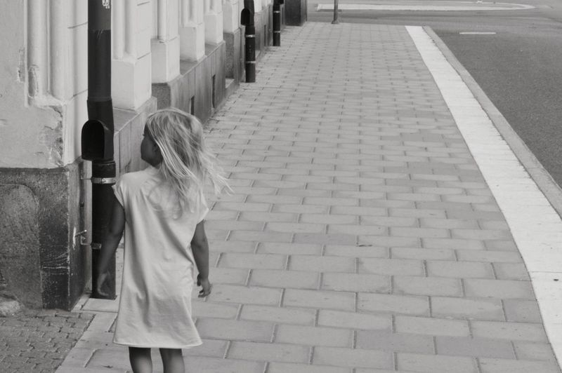 Rear View Of Girl Standing On Sidewalk
