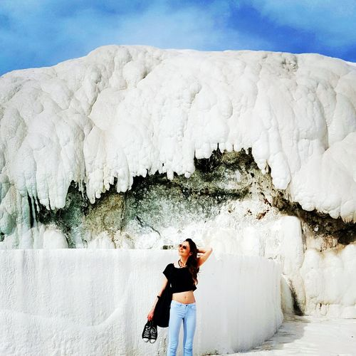 Fashionable Young Woman Holding Shoes Against Limestone At Pamukkale
