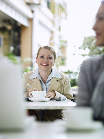 Smiling Businesswoman Sitting With Coffee At Sidewalk Cafe