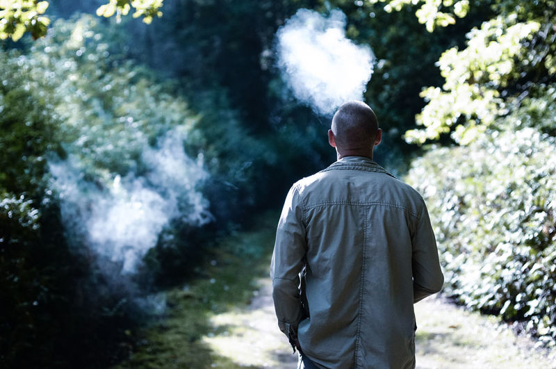 Rear view of man smoking while standing forest