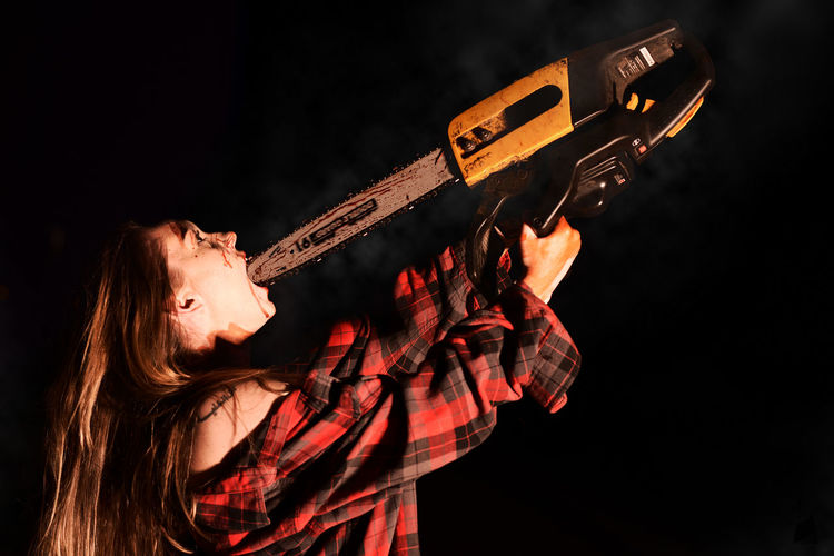 Young Woman Putting Chainsaw In Mouth At Night