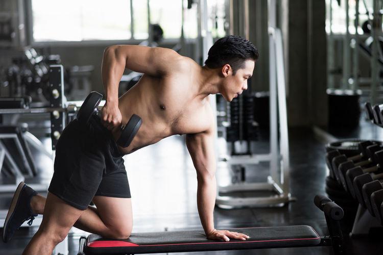 Young shirtless man exercising in gym