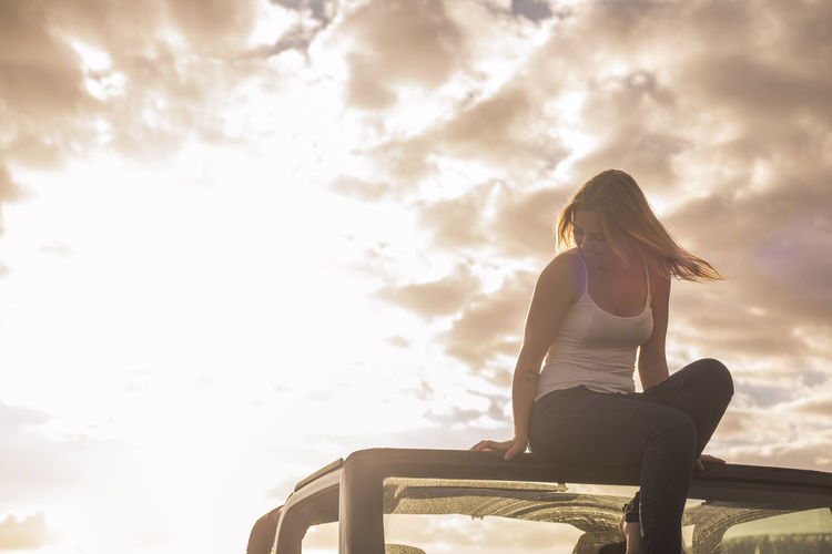Low angle view of young woman sitting on car roof against sky during sunset