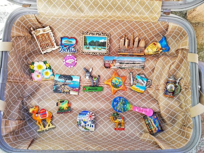 open suitcase with souvenir magnets Multi Colored Suitcase Open Concept Vacations Trips Trips Around The World Magnets Souvenirs Travel Holidays